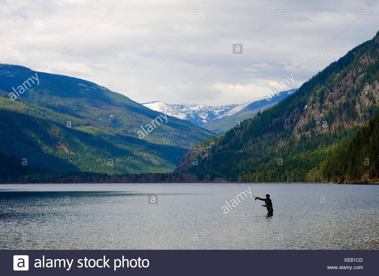 Joven de la pesca con mosca en el lago cerca de lumby Mabel en la región de Okanagan de la Columbia Británica, Canadá Imagen De Stock
