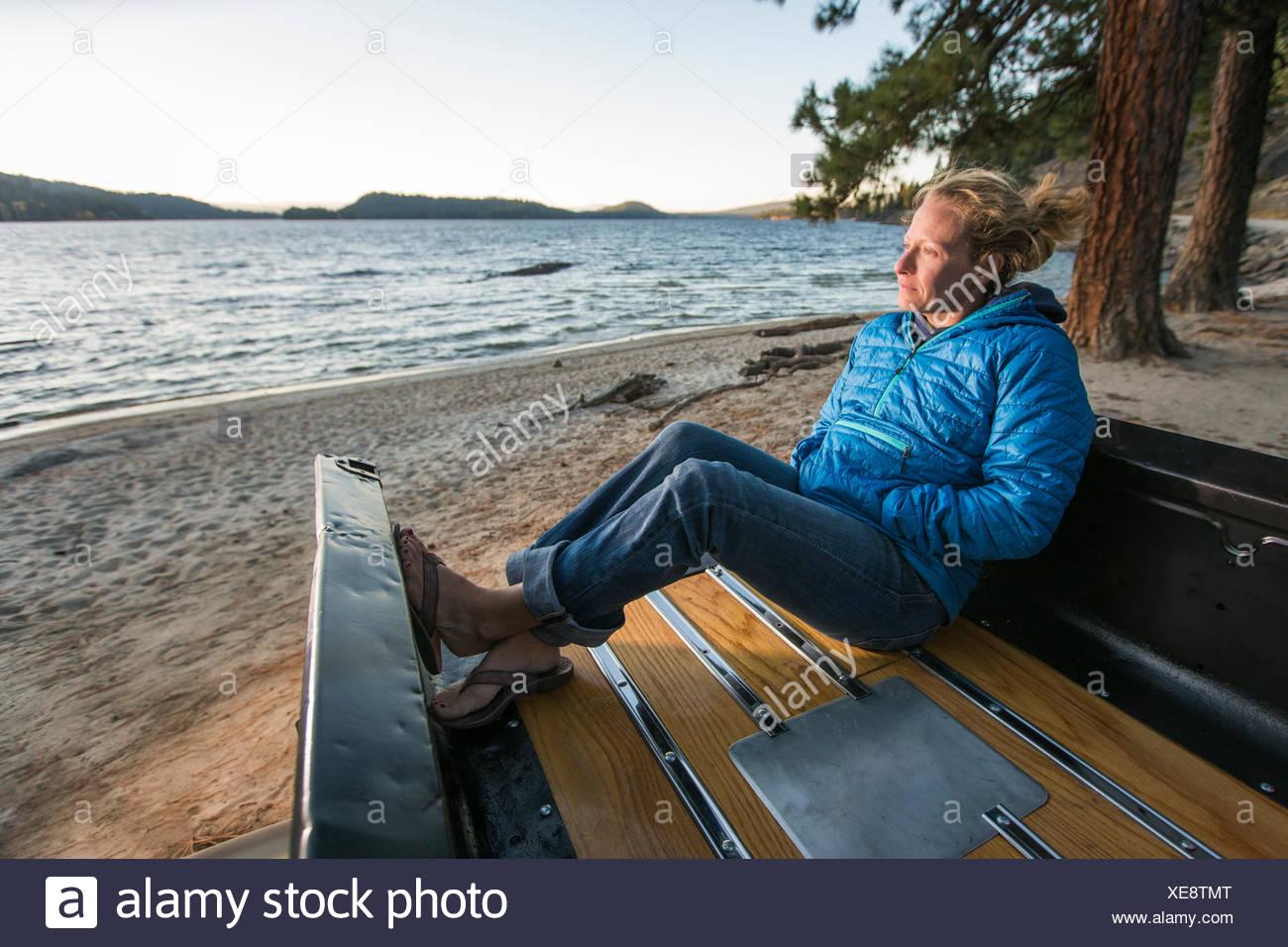 Mujer sentada en un renovado camión viendo el atardecer, Payette Lago, McCall, Idaho, EE.UU. Foto de stock