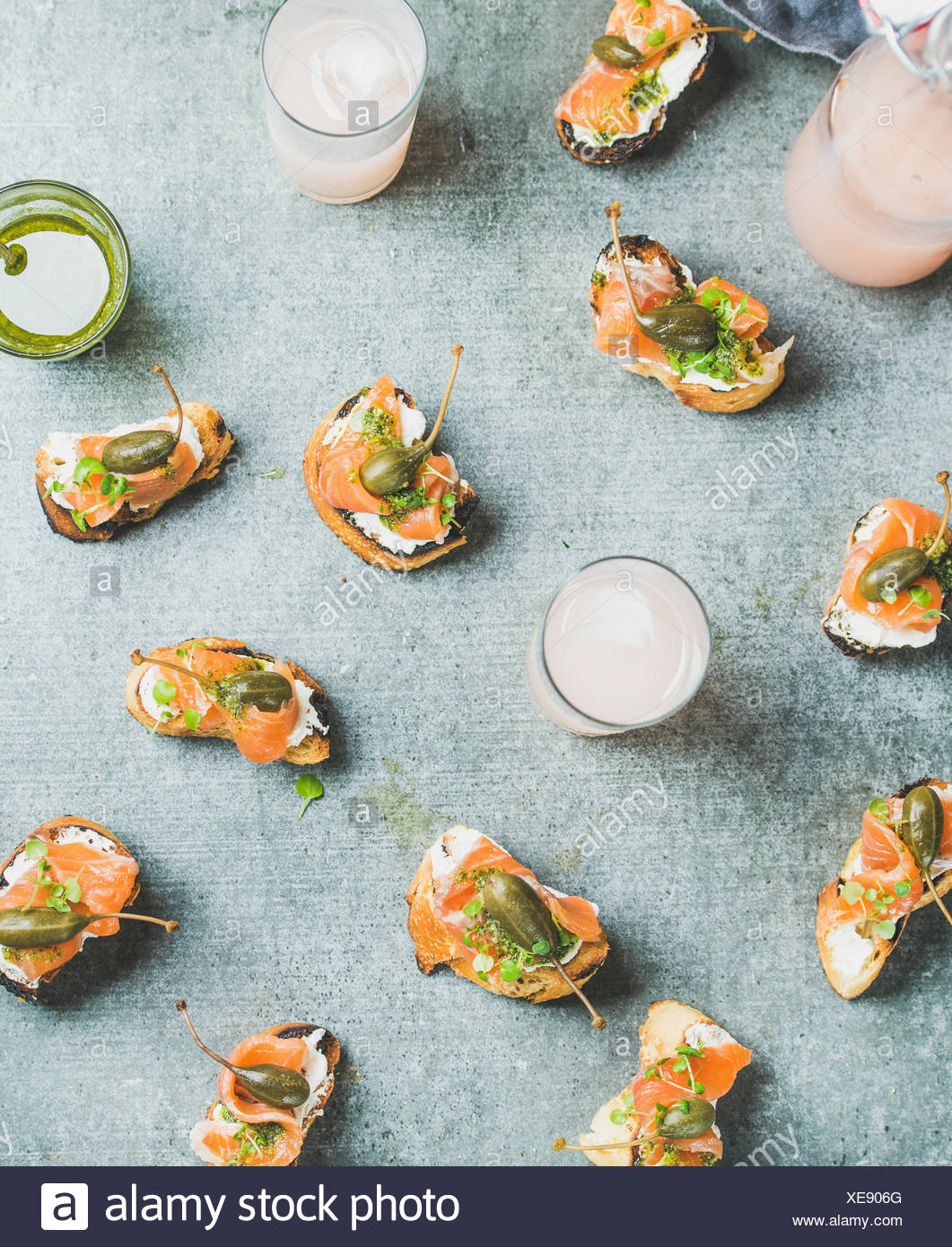 Crostini con salmón ahumado, salsa pesto, berro y alcaparras y cócteles de pomelo rosa sobre fondo gris, vista superior, flay-lay. Parte, caterin Foto de stock