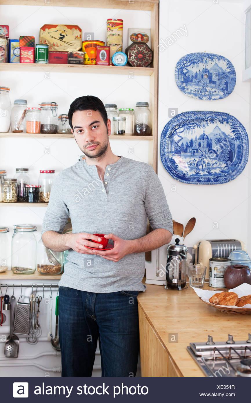 Mitad hombre adulto de pie en la cocina sosteniendo la taza de café Imagen De Stock