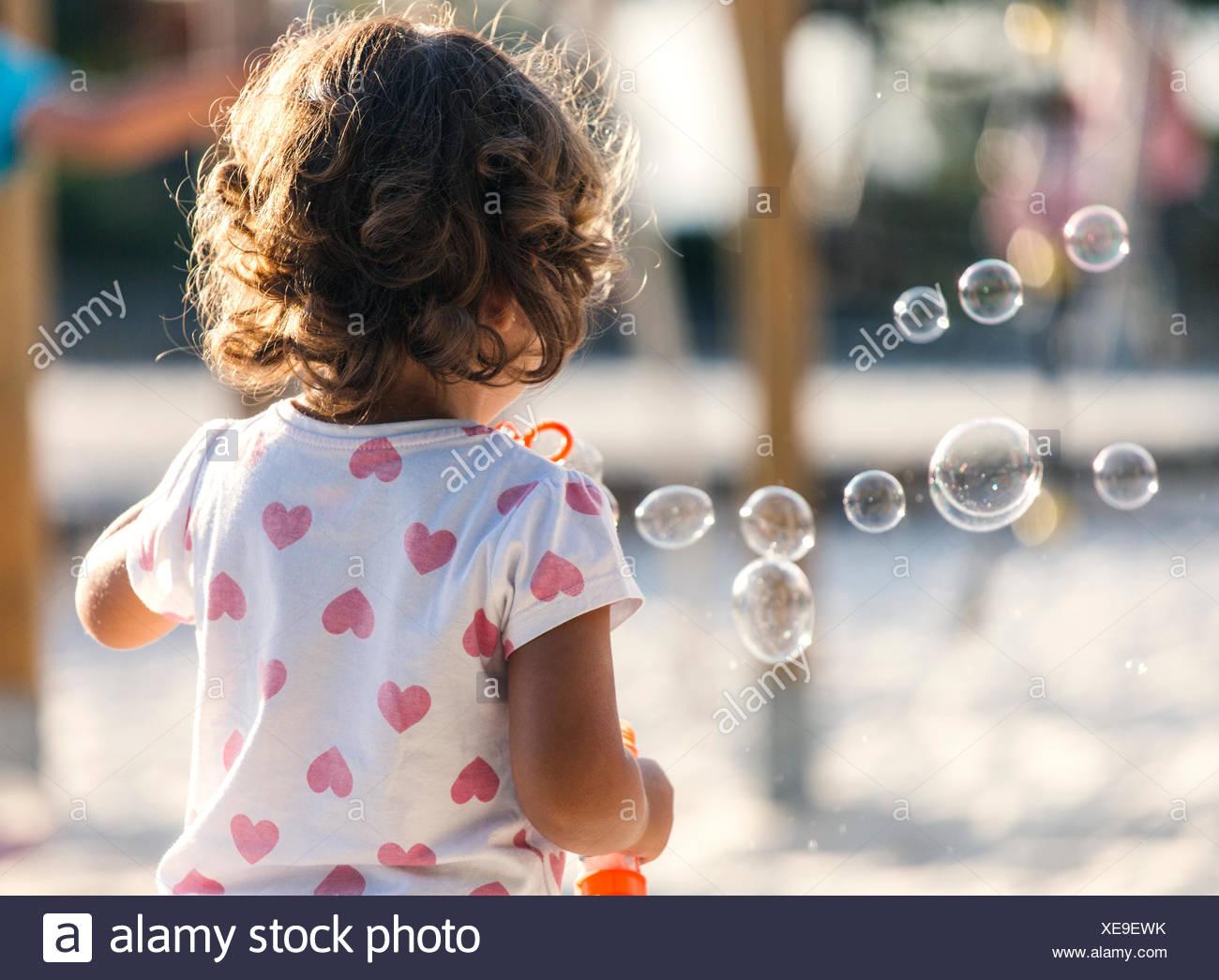 Vista posterior de la niña haciendo burbujas de jabón en el patio Imagen De Stock