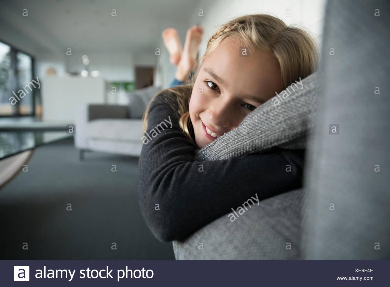 Retrato chica sonriente sentando en el sofá Imagen De Stock