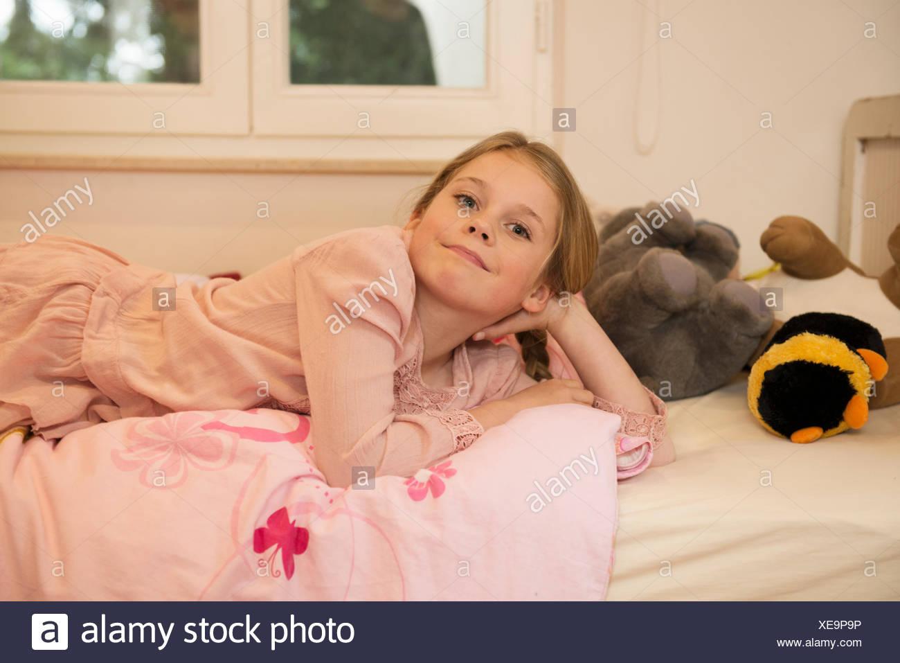 Retrato de traviesos chica acostada en la cama Imagen De Stock