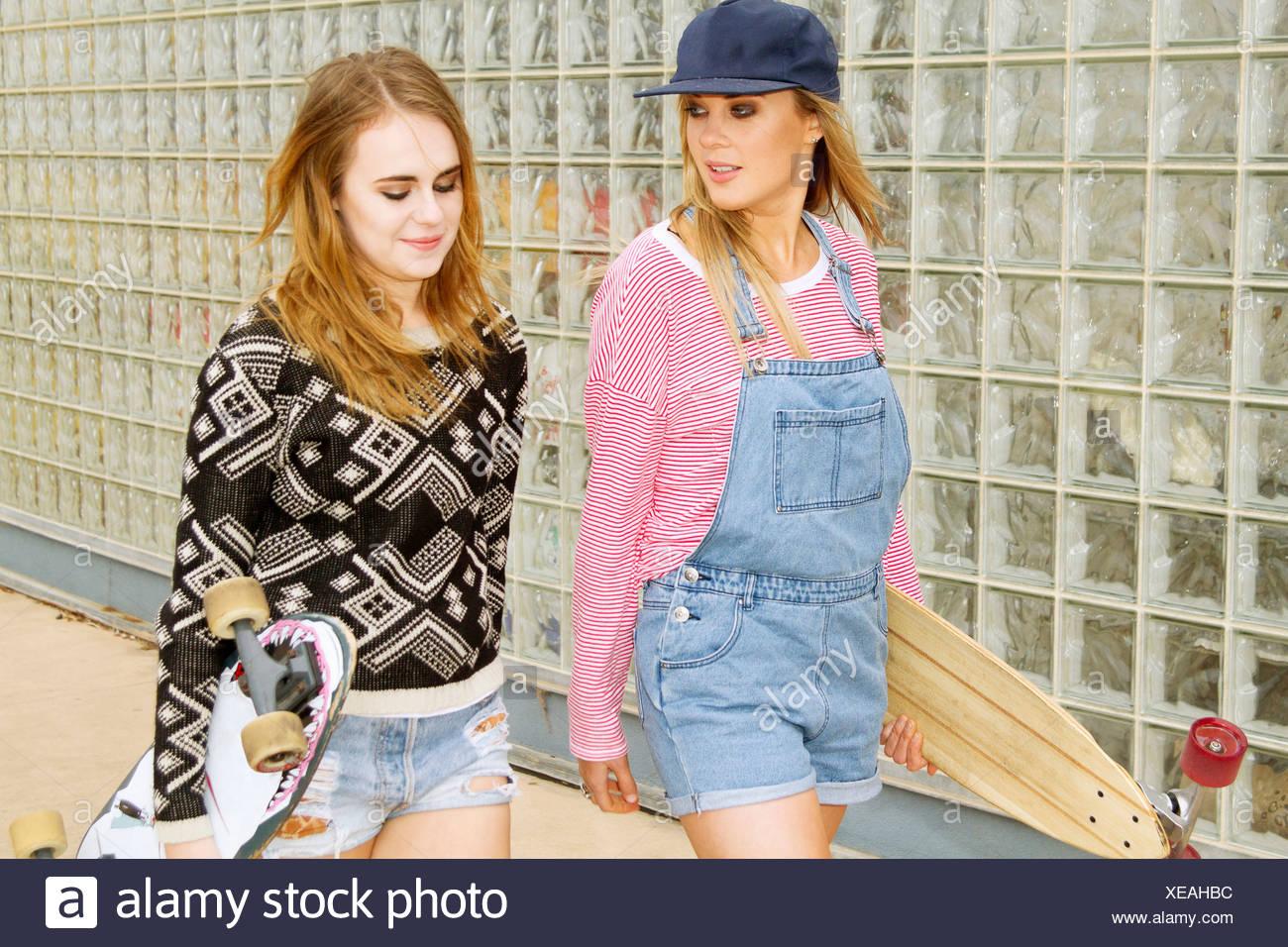 Dos jóvenes mujeres que llevaban skateboards junto a una pared de cristal Imagen De Stock