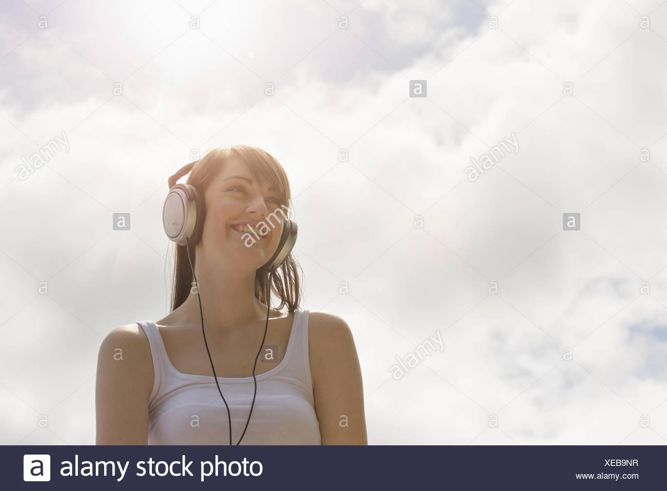 b0c8d328008 Mujer joven con los auriculares puestos bajo el cielo soleado Imagen De  Stock
