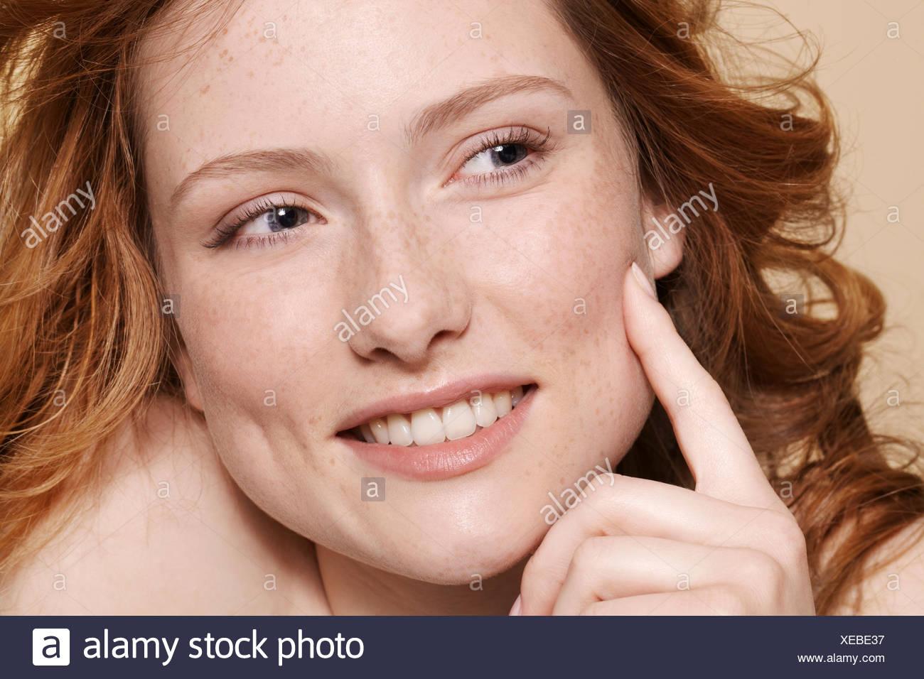 Foto de estudio de la mujer joven con pelo rojo rizado, con la mano en el mentón apuntando Imagen De Stock