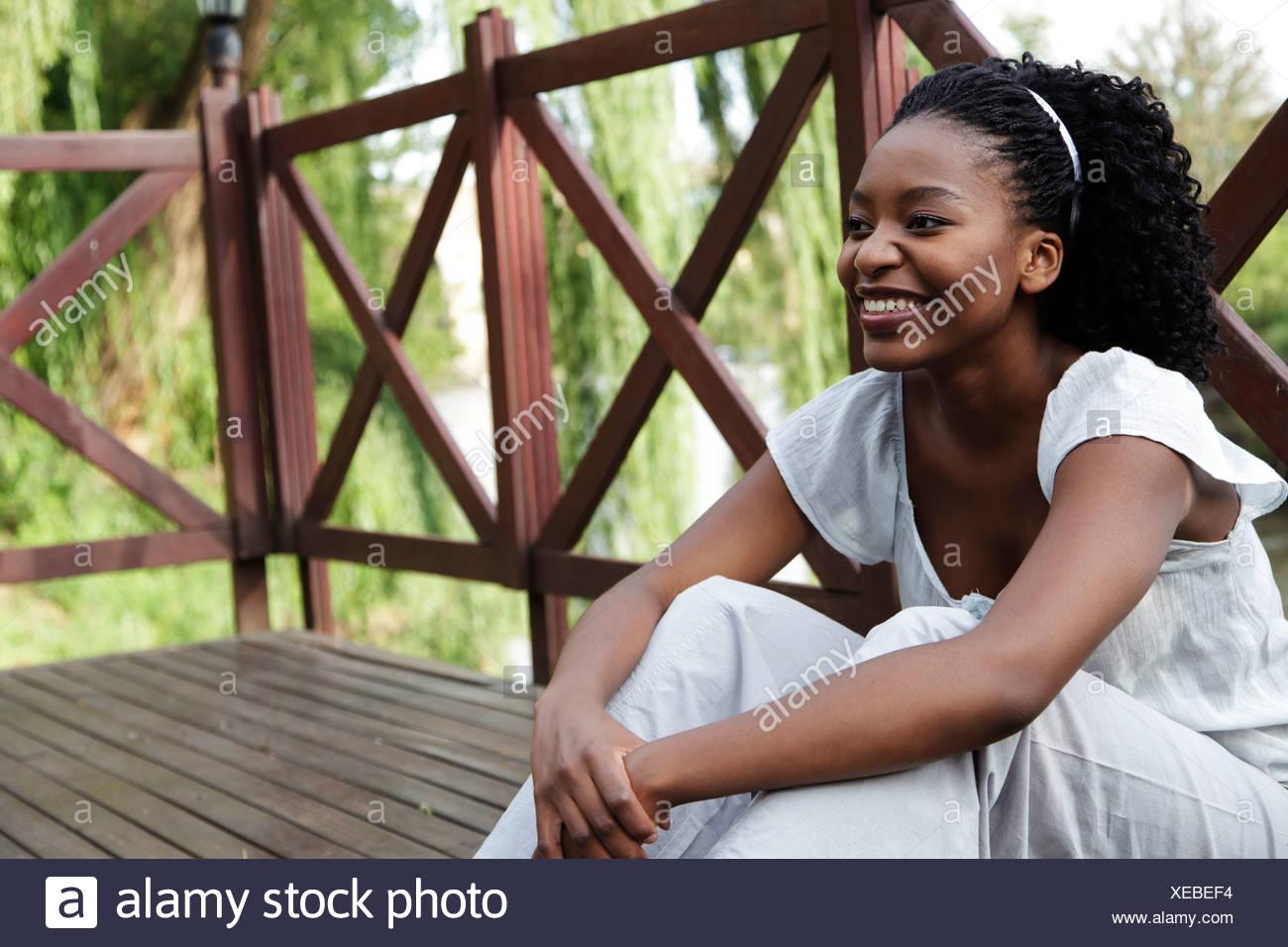 Joven africana se asienta sobre una plataforma de madera Foto de stock