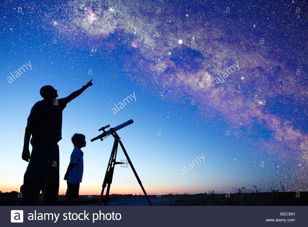 Hombre mostrando vía láctea a chico, telescopio Imagen De Stock