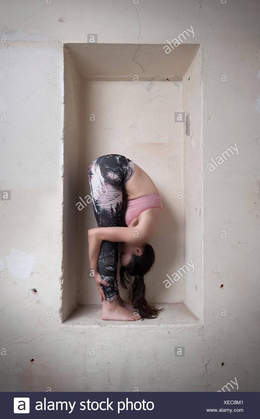 Mitad mujer adulta practicando uttanasana pose en la alcoba, Munich, Baviera, Alemania Imagen De Stock