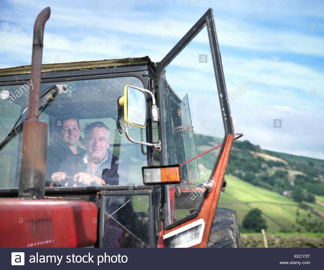 Agricultor y su hijo en la cabina del tractor, Retrato Imagen De Stock