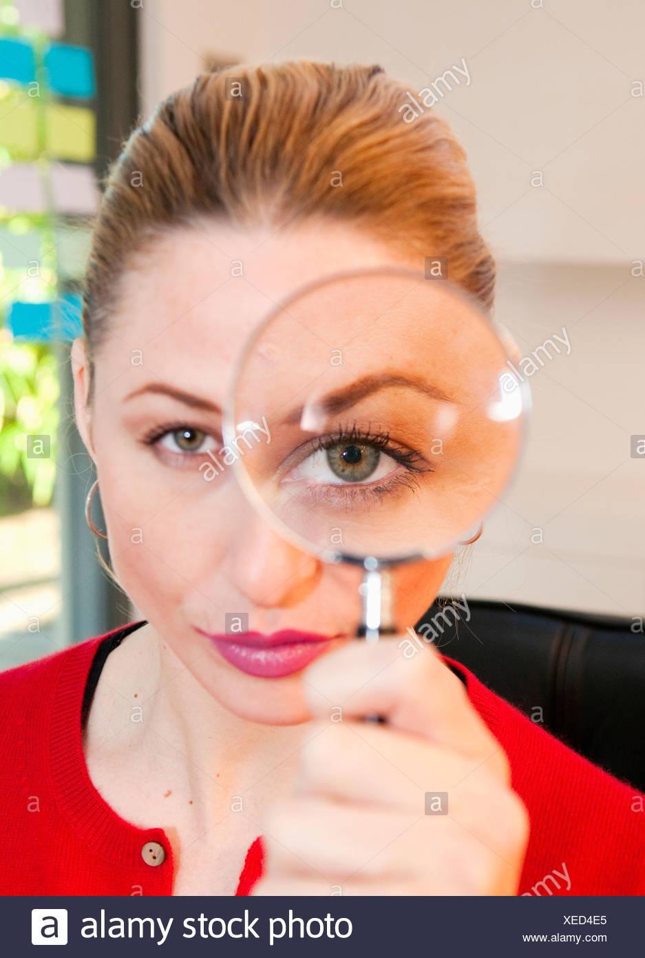 Mujer mira a través de la lupa Foto de stock