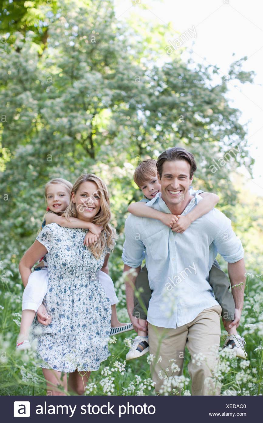 Los padres llevan a sus hijos al aire libre piggyback Foto de stock