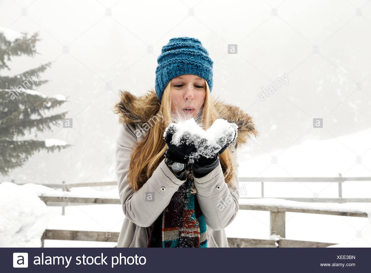 Mujer joven puñado de soplado de nieve Imagen De Stock