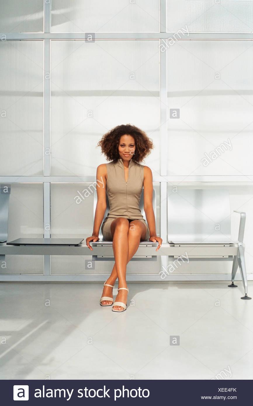 Una joven en un vestido sin mangas, sentado en un banco. Imagen De Stock