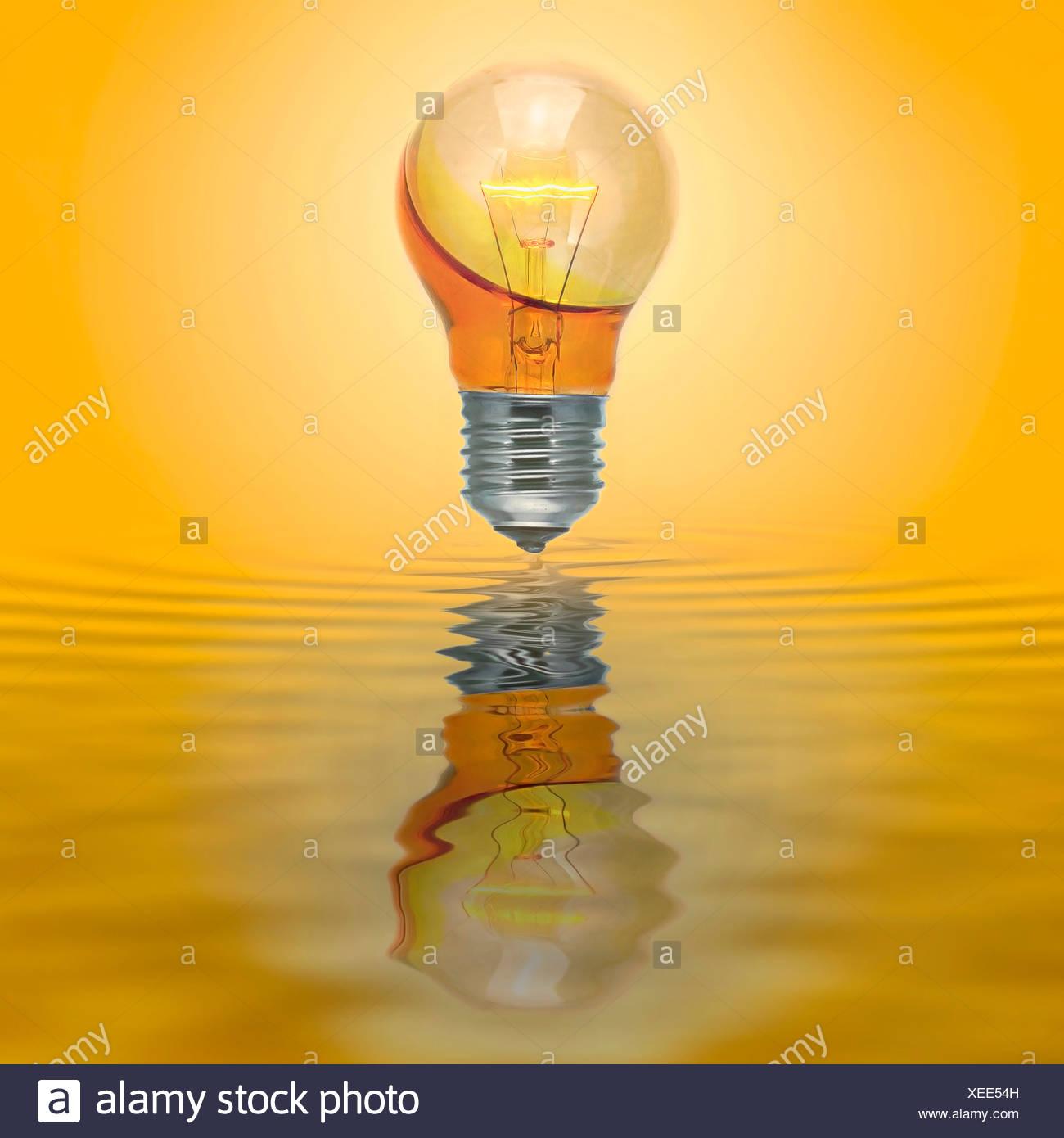 Bombilla ilumine con ninguna conexión eléctrica llena con agua amarilla. Imagen De Stock