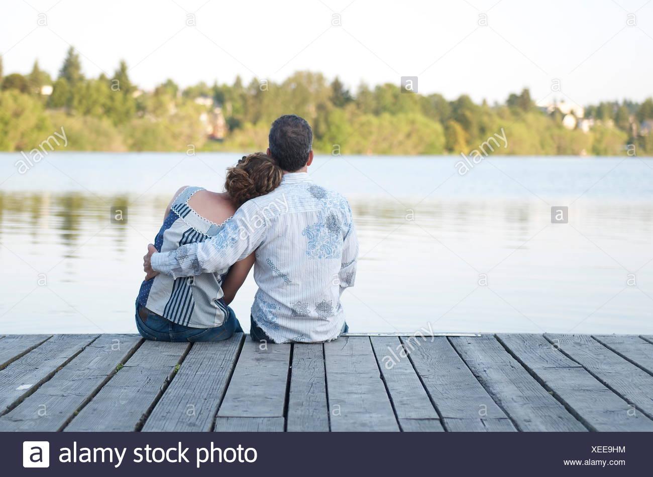 Vista trasera de una pareja sentada en un muelle de madera abrazando Imagen De Stock