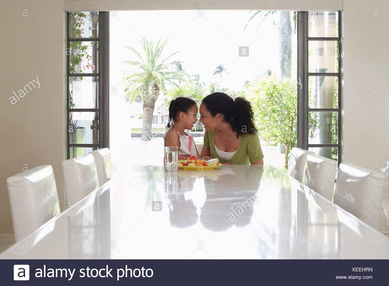 Madre e hija (5-6 años) sentados en la mesa de comedor Imagen De Stock