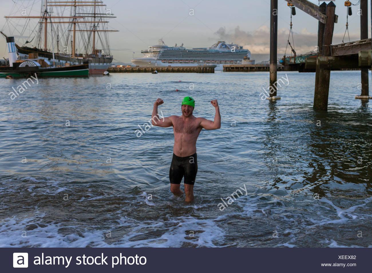 Hombre en natación troncos flexionando los músculos mientras está de pie en el agua, el Dolphin club, san Francisco, California, EE.UU. Imagen De Stock