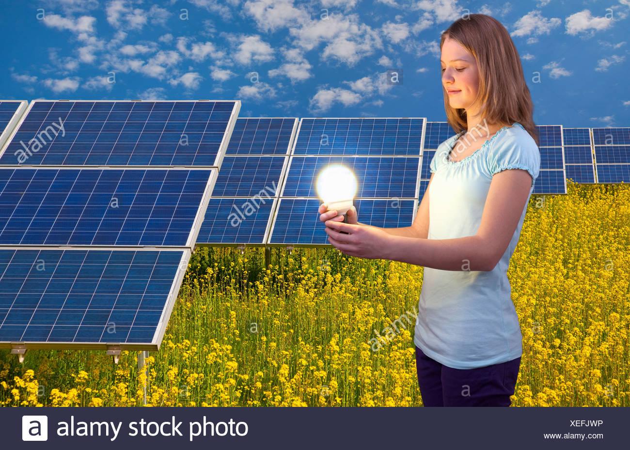Mujer con bombilla y paneles solares Imagen De Stock