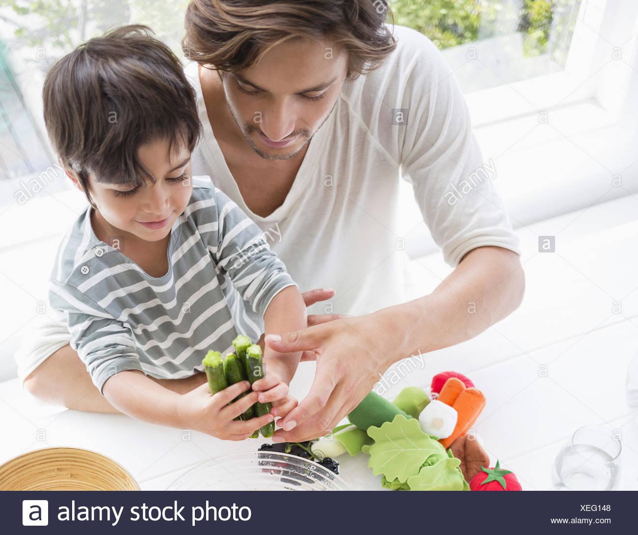 Feliz familia joven preparar verduras en casa Imagen De Stock