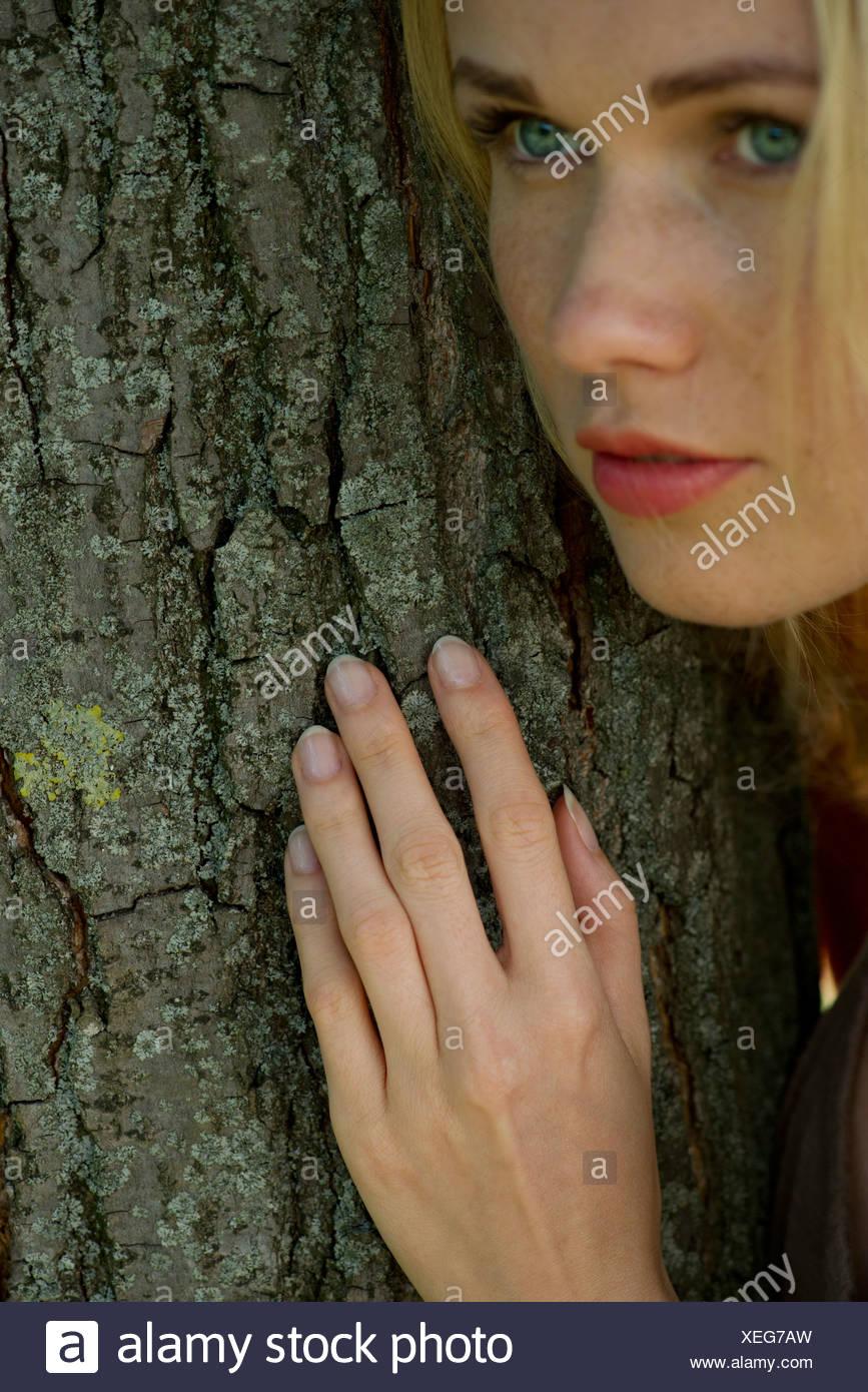 Mujer joven RECOSTADA contra el tronco del árbol con expresión soñadora Imagen De Stock