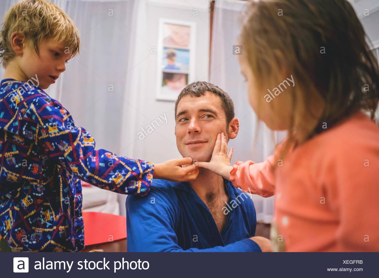 Chico y chica tocar cara afeitada del hombre. Foto de stock