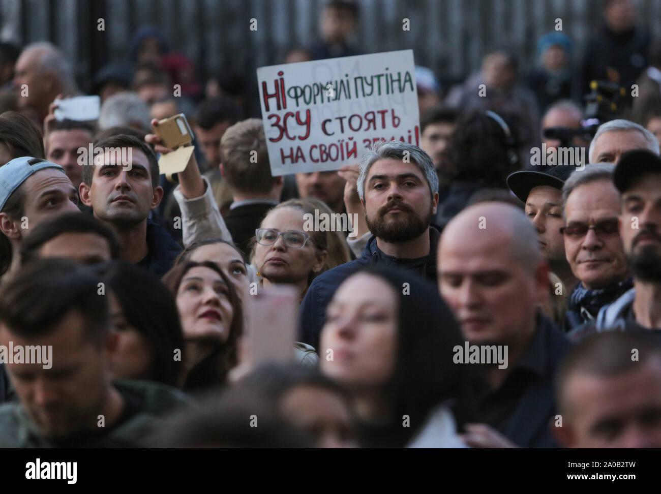 Kiev, Ukraine. 19 Sep, 2019. Les gens se tiennent près d'une pancarte qui dit ''pas de formule de Poutine. L'armée ukrainienne est sur ses propres terres'' comme ils se réunissent à l'avant du bureau présidentiel pour protester à Kiev, Ukraine, le 19 septembre 2019. Des centaines d'Ukrainiens sous le slogan ''Le complot de Norman est une trahison!'' se réunissent à l'avant du bureau présidentiel pour protester contre la mise en œuvre des accords conclus dans le cadre de la formule de M. Steinmeier lors de la réunion. format Normandie Credit: Sergii Kharchenko/ZUMA/Alamy Fil Live News Banque D'Images