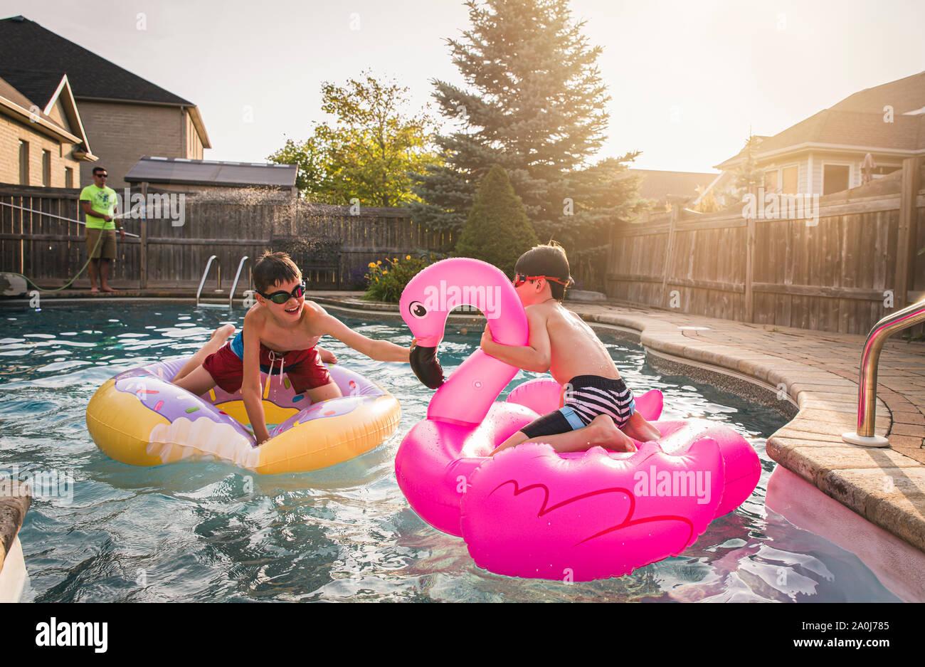 Deux garçons jouant dans une piscine sur piscine gonflable jouets. Banque D'Images