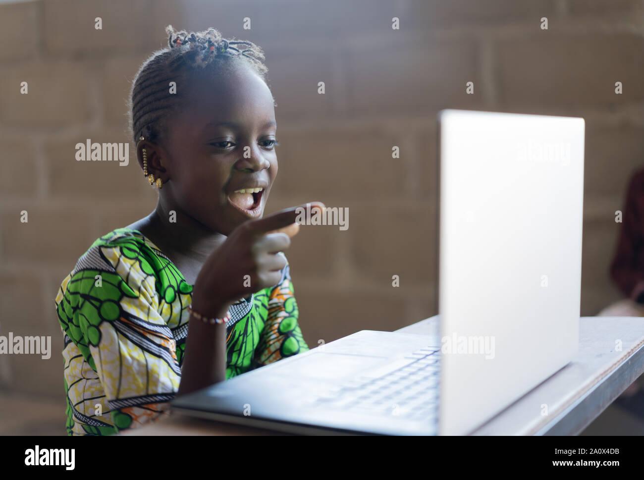 L'Afrique de l'adorable petite fille surpris Looking at Laptop Computer Technology Banque D'Images
