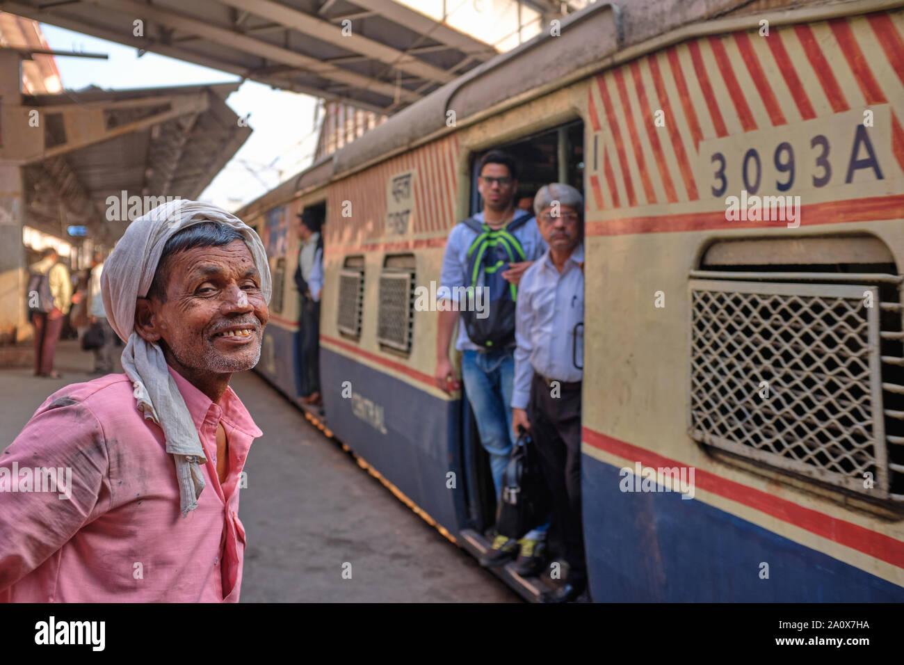 Un heureux porteur de Maharaj Chhatrapati Shivaji Terminus (CSMT) à Mumbai, Inde, en attente de l'arrivée d'un train local pour transférer ses biens Banque D'Images
