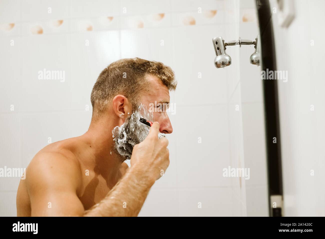 Man shaving face au miroir de salle de bains Banque D'Images