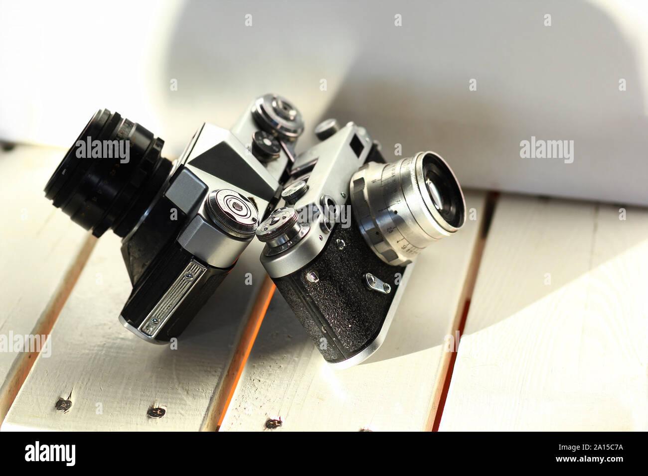 Deux noirs vintage old-school caméras photo film blanc sur les planches en bois, intérieur ensoleillé Banque D'Images