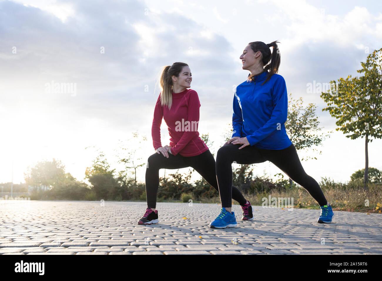 Les femmes s'étend ses jambes dans le parc Banque D'Images