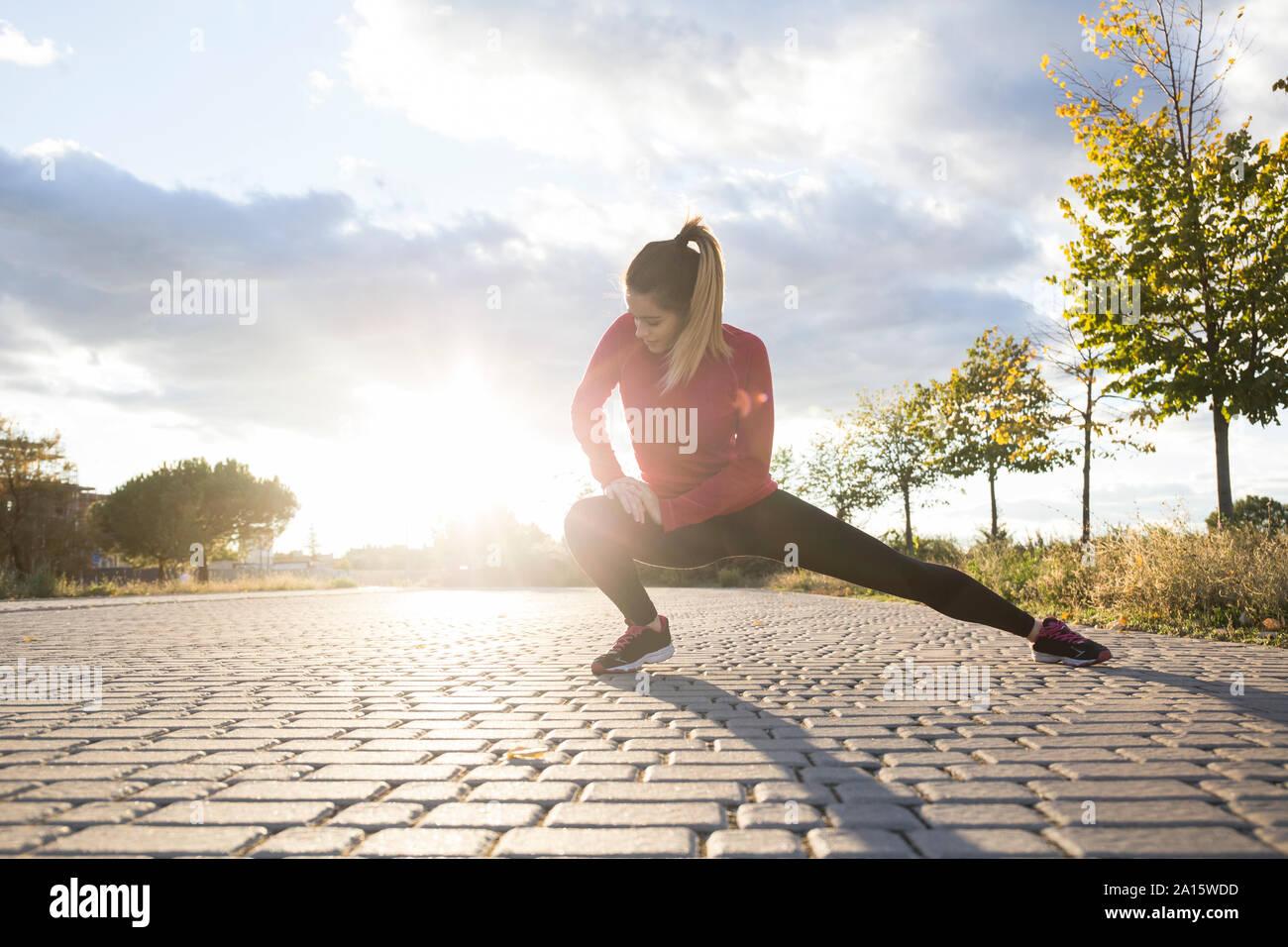 Jeune femme étend sa jambe dans un parc Banque D'Images