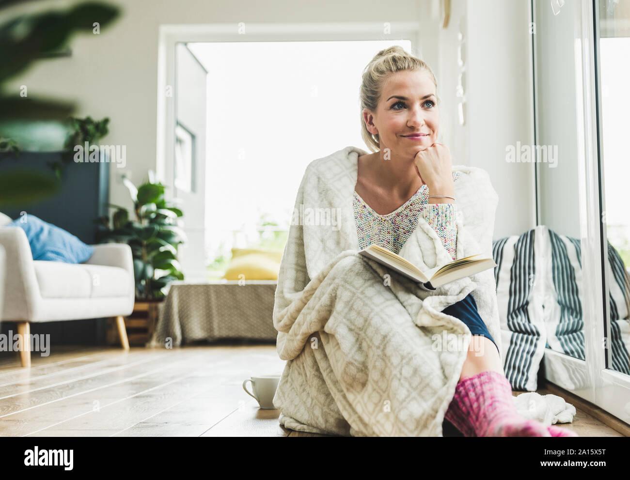 Femme enveloppée dans une couverture assis à la fenêtre à la lecture d'un livre Banque D'Images