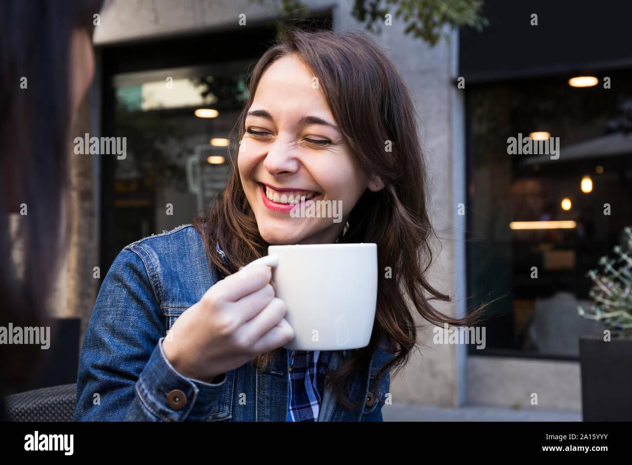 Happy young woman laughing with eyes closed et holding Coffee cup de café à l'extérieur de Madrid, Espagne Banque D'Images