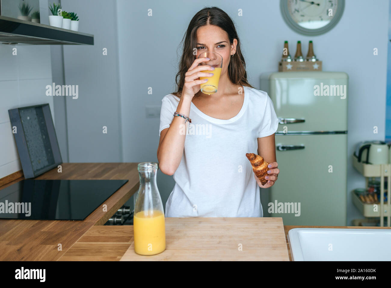 Jeune femme ayant le petit déjeuner avec du jus de fruit et un croissant dans la cuisine Banque D'Images