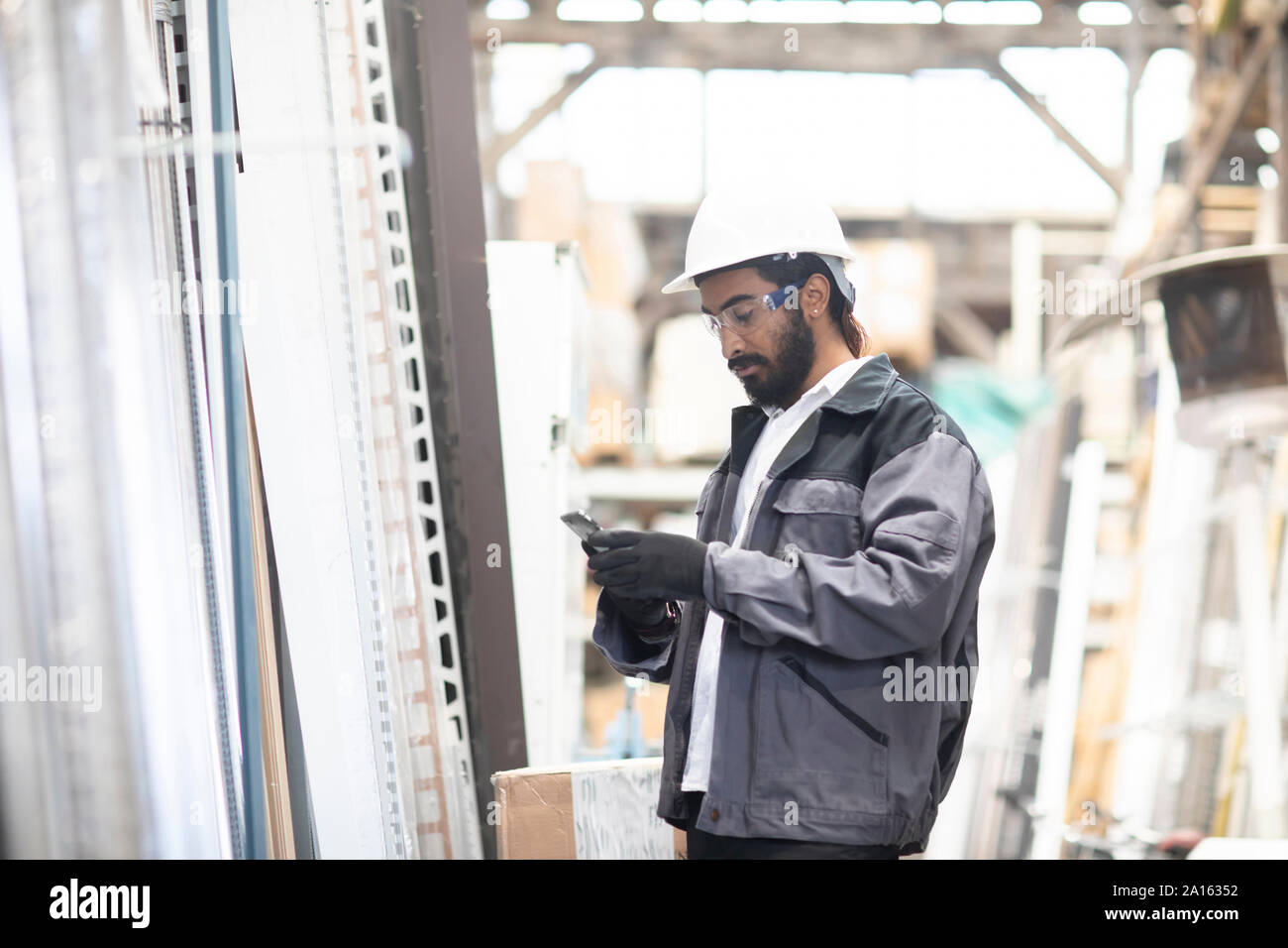 Jeune homme avec cell phone wearing hard hat travaillant dans un entrepôt Banque D'Images