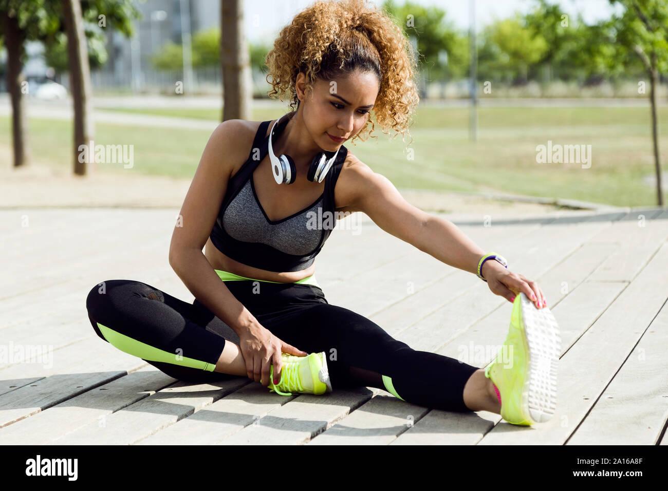 Sporty woman stretching dans le parc Banque D'Images