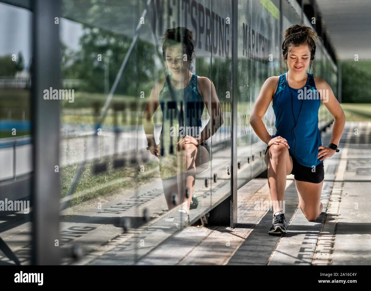 Jeune femme sportive portant des écouteurs et de faire l'exercice d'étirement Banque D'Images