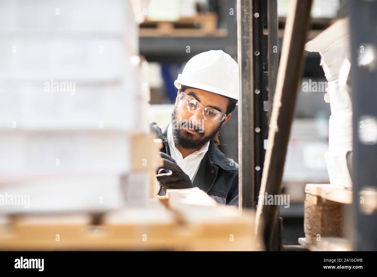 Young man wearing hard hat travaillant dans un entrepôt Banque D'Images