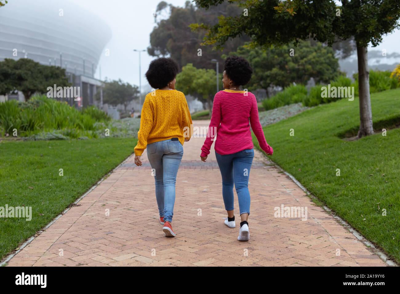 Deux jeunes femmes marchant ensemble dans un parc Banque D'Images