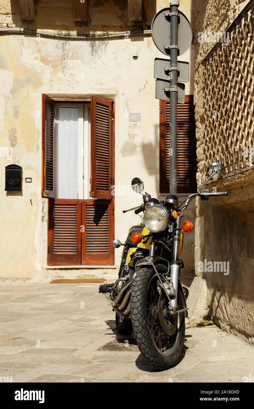 Vintage moto jaune debout dans la rue de la vieille ville italienne. Lecce, Pouilles, Italie Banque D'Images