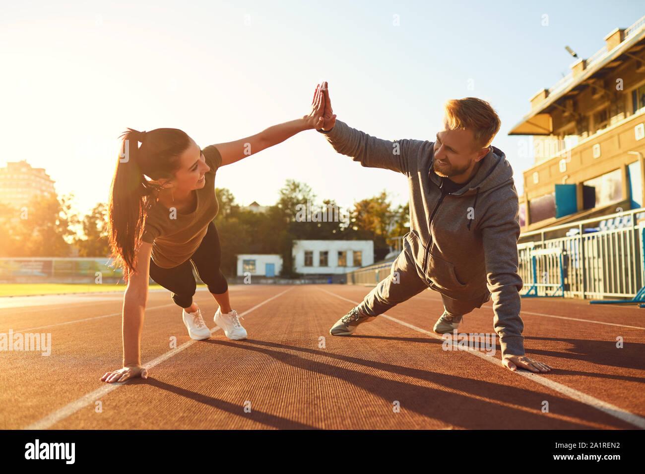 Jeune couple doing pushups dans le stade Banque D'Images