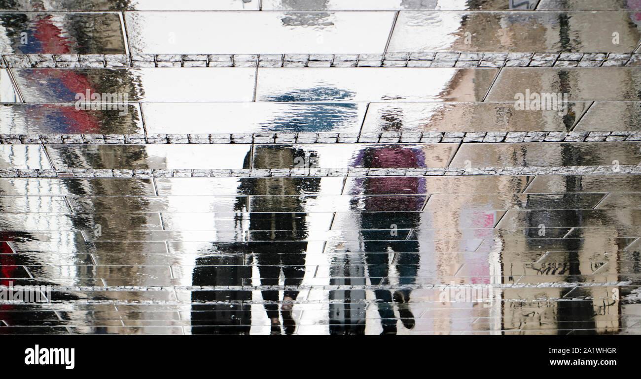 Réflexion floue d'ossature sur humide ville rue de deux personnes marcher sous parapluie et tirant voyageant rentrer dans la journée d'automne pluvieuse Banque D'Images