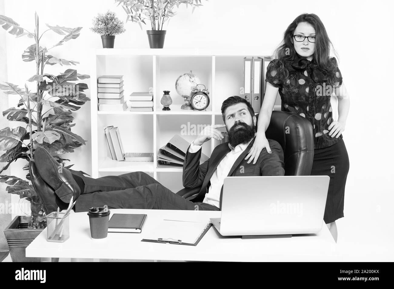 Bureau patron paresseux. Offrir un massage. Hipster barbu homme patron s'asseoir dans un fauteuil en cuir de l'intérieur du bureau. Patron et secrétaire girl au lieu de travail. Relations au travail. Les gens d'affaires et le personnel du concept. Banque D'Images