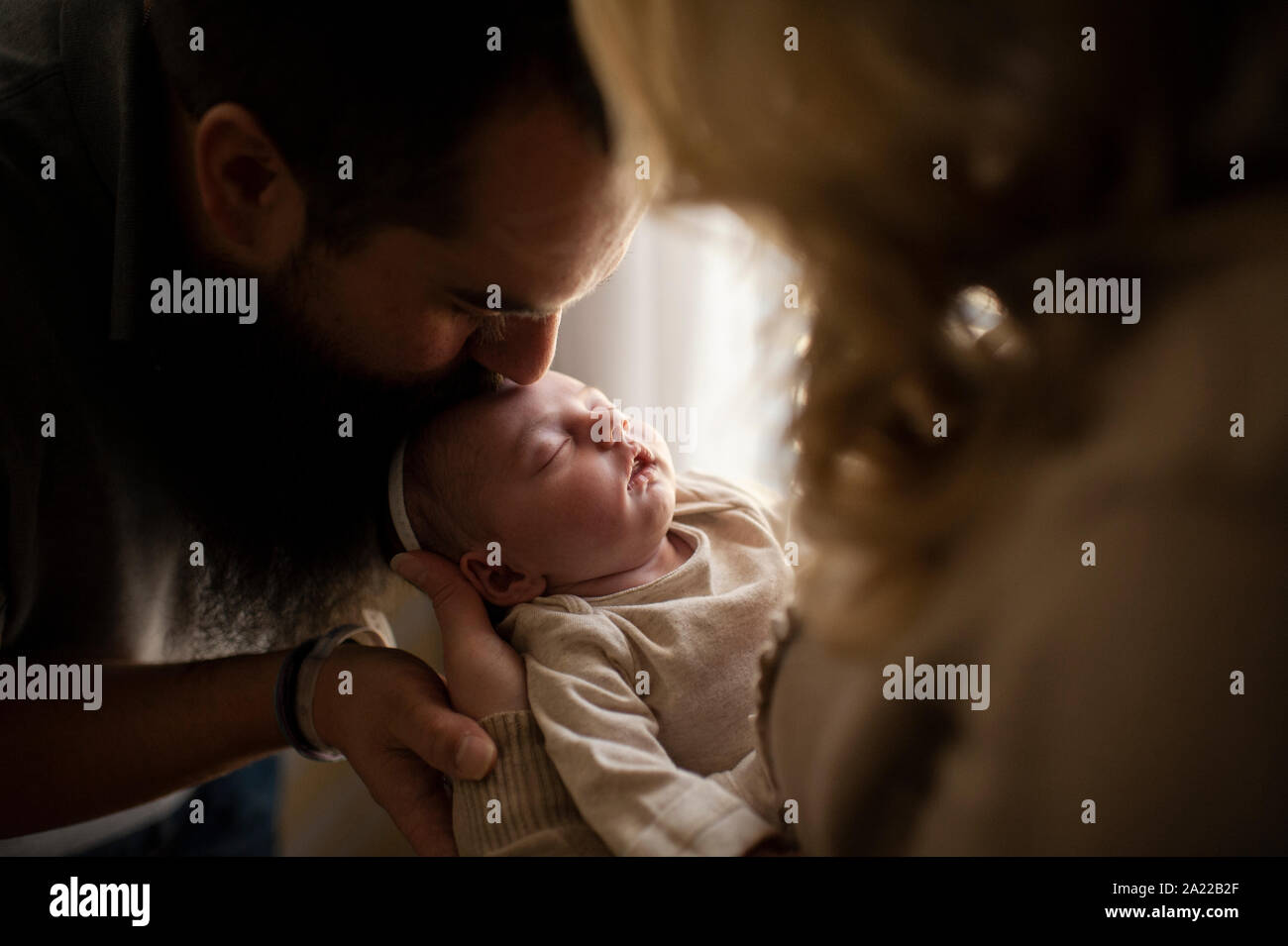 Father kissing filles nouveau-né endormi dans les bras de la mère de la tête Banque D'Images