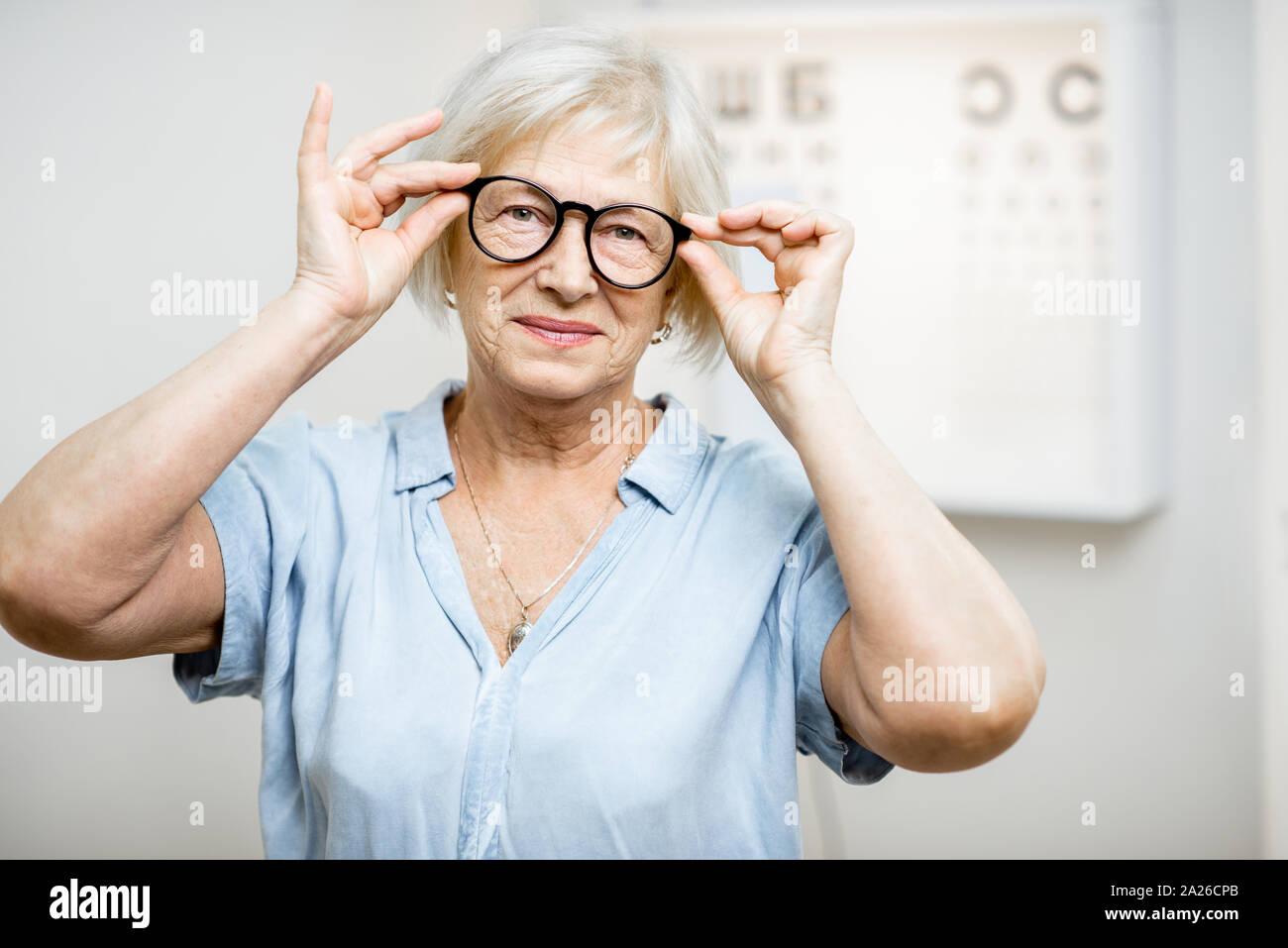 Portrait of a senior woman wearing eyeglasses en face de l'office en ophtalmologie. Concept de contrôle de la vue et de la sélection de verres Banque D'Images