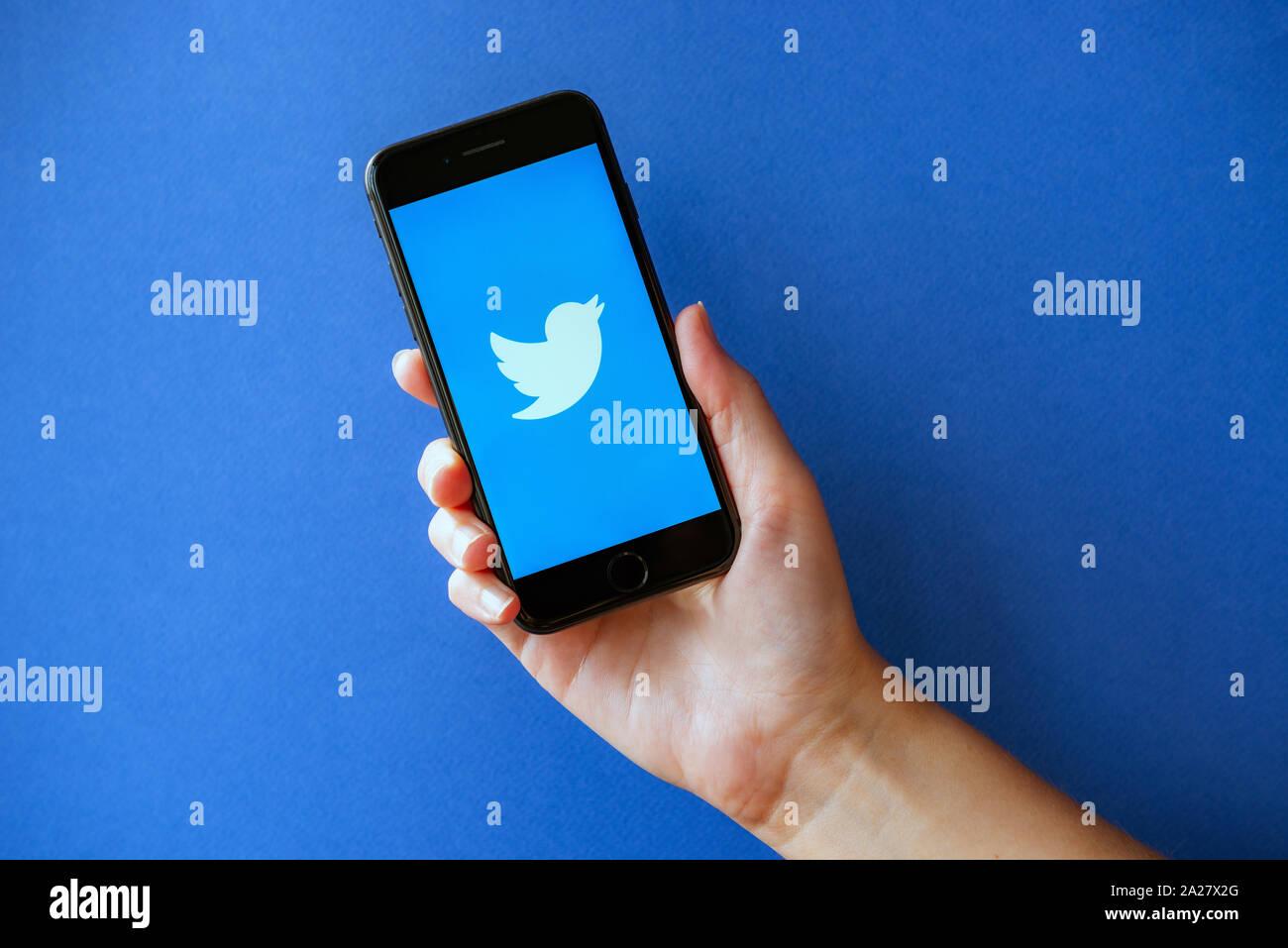 Kiev, Ukraine - 1 octobre 2019: Studio shot of hand holding Apple iPhone 8 avec Twitter logo sur un écran. Isolé sur un fond de papier bleu. Banque D'Images