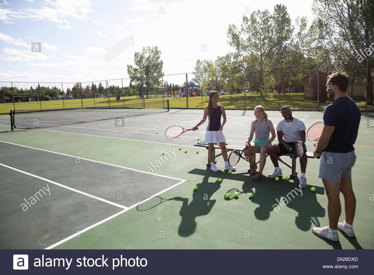 Les jeunes couples se préparant à jouer au tennis sur un court de tennis ensoleillé Banque D'Images